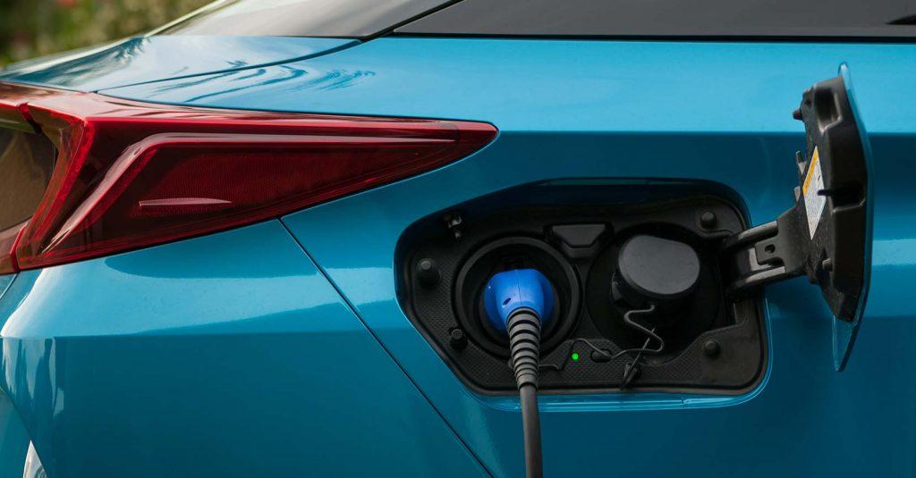 sininen hybridiauto jonka latauspistoke on auki