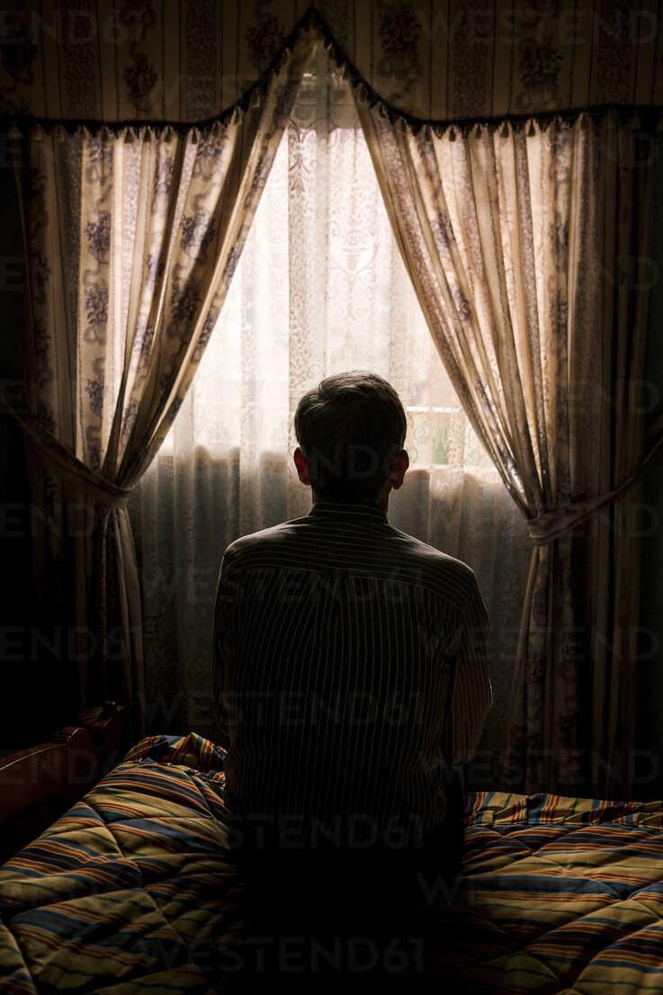 https www westend61 de en imageview cavf57391 rear view of senior man sitting on bed against curtains hanging window in darkroom