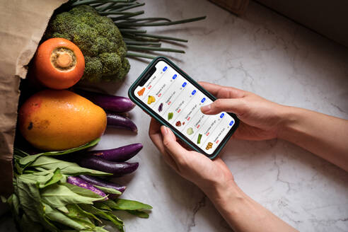 Unrecognizable female with smartphone with mobile app for online shopping  taking fresh groceries from delivery man - ADSF15002 - ADDICTIVE STOCK  CREATIVES/Westend61