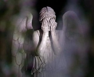 A Weeping Angel covering its eyes