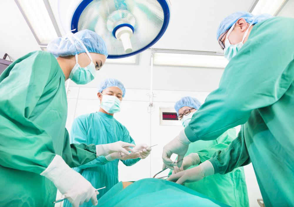 https://i2.wp.com/images.wisegeek.com/four-surgeons-in-green-gowns-and-masks-standing-over-patient.jpg
