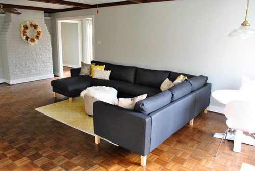 dark gray Karlstad ikea sectional sofa recently assembled in gray living room with fireplace