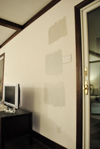 three Benjmain Moore gray paint color swatches on a white wall at night time in artificial light