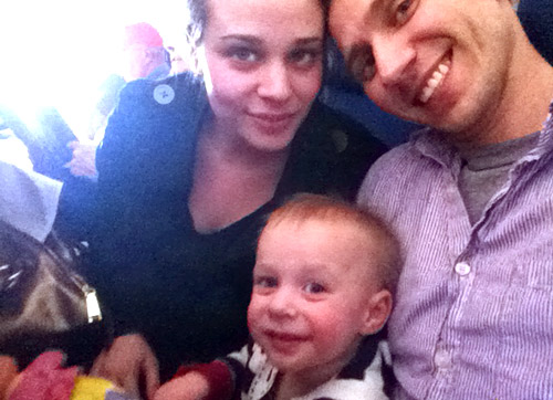 family selfie on airplane with 1 year old