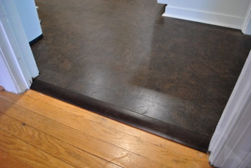 How To Add Floor Trim  Transitions  and Reducers   Young House Love Oh but remember we re eventually going to be refinishing the rooms with the  orange wood flooring to match the darker cork tone  so it should look  something