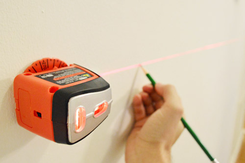 using a black & decker laser level and pencil to mark a level line on a wall