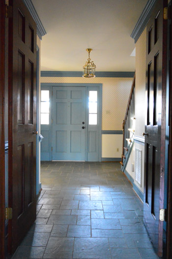 before photo of 1980s entryway foyer with williamsburg blue trim, dark wood molding, wallpaper, and discolored slate tile floor