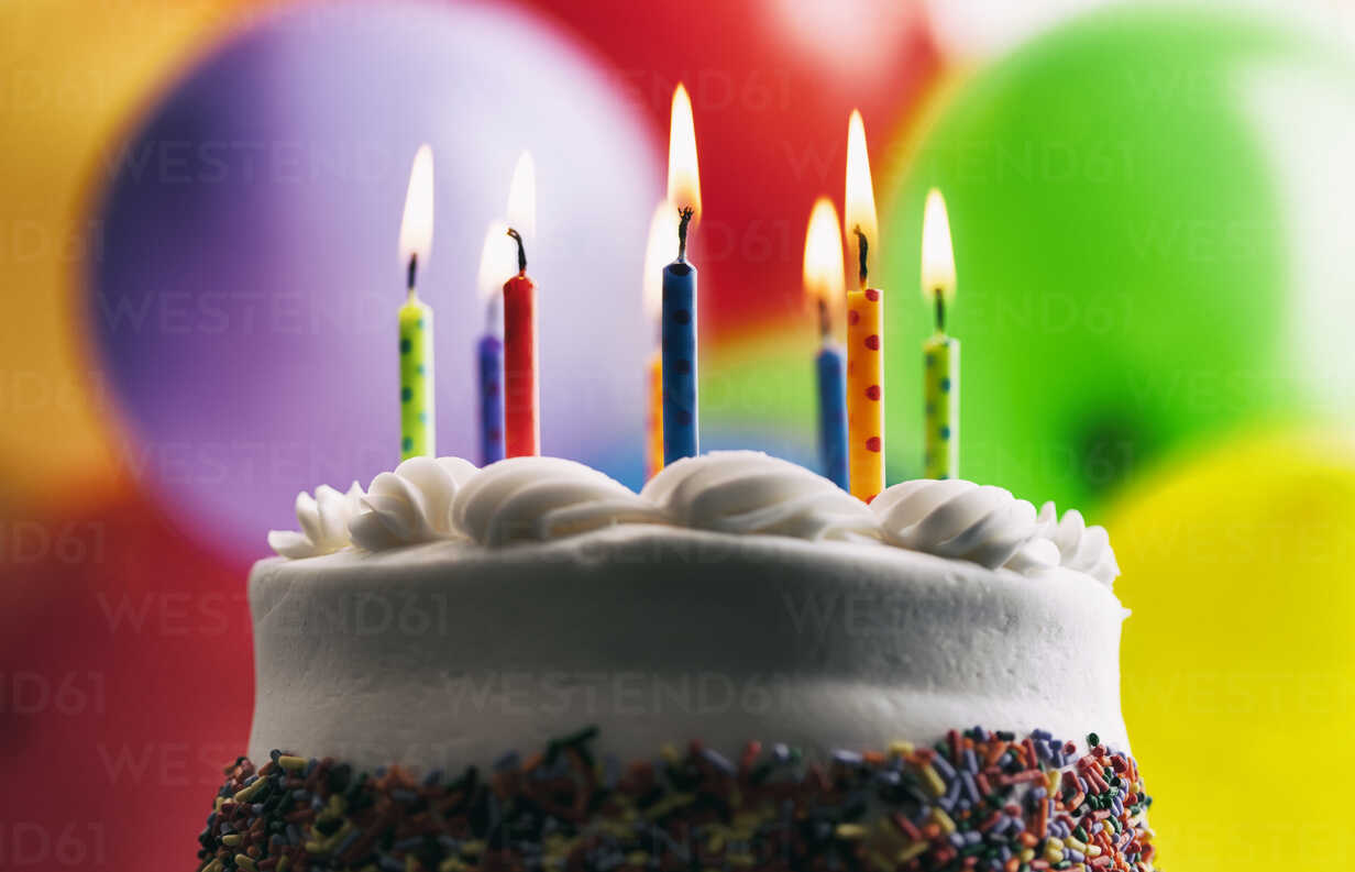 Lighted Birthday Candles On A Cake In Front Of Balloons Stockphoto