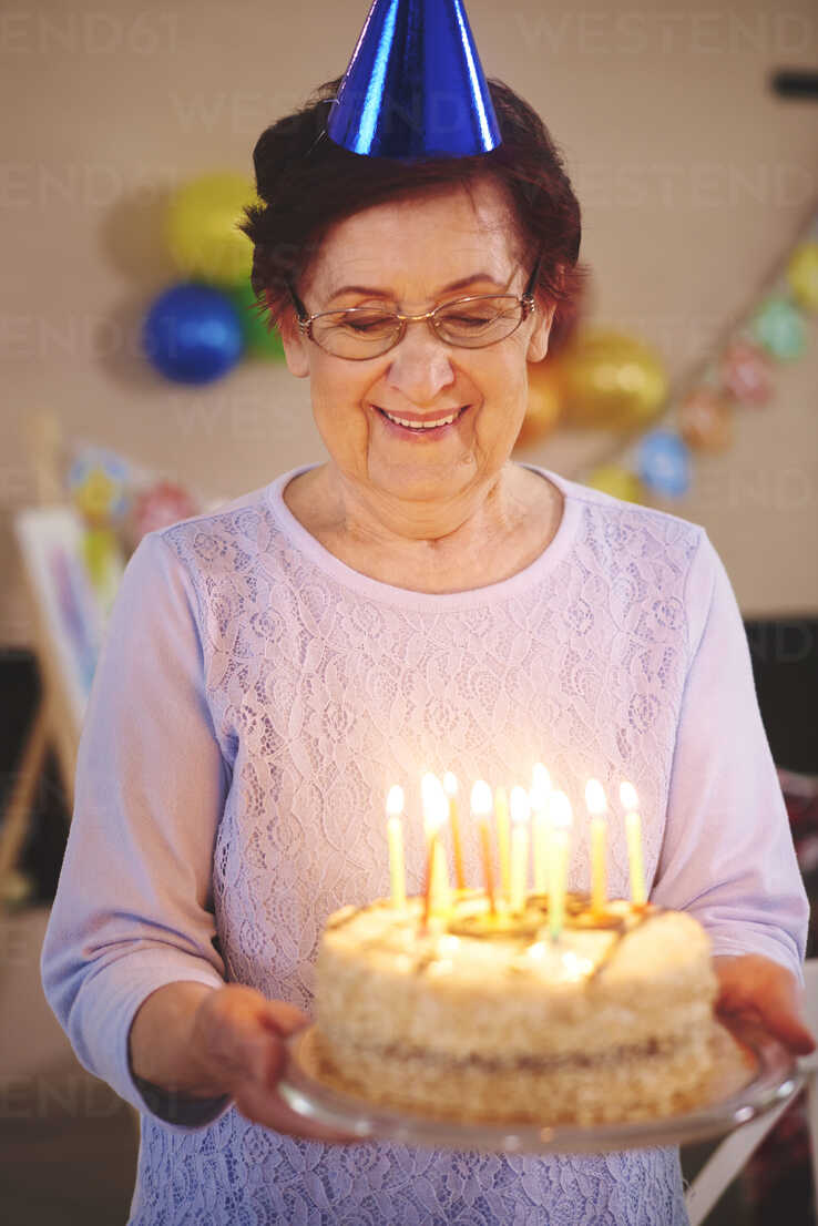 Senior Woman With Birthday Cake At Party Stockphoto