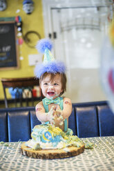 Baby Boy Wearing Party Hat Smashing First Birthday Cake At Table Stockphoto