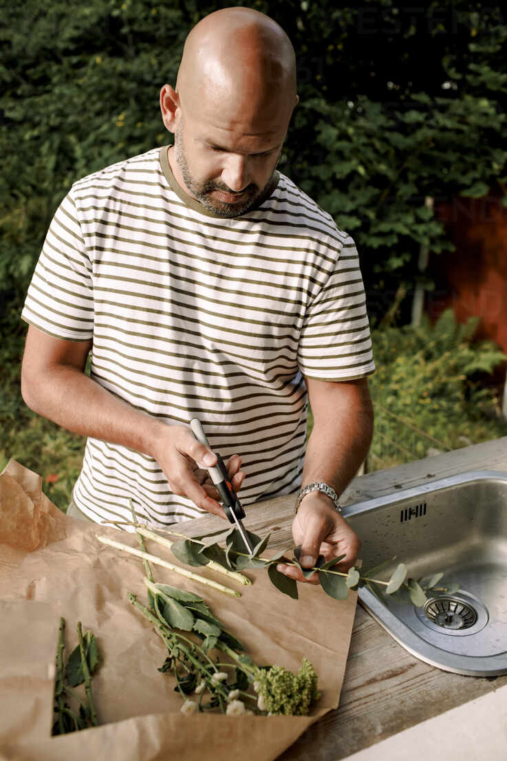 https www westend61 de en imageview masf20942 mature man cutting plant stem while standing by sink in yard