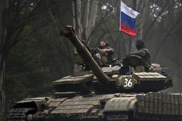 In this Sunday, July 29, 2015, file photo, a pro-Russian rebel looks up while riding on a tank flying Russia's flag, on a road east of Donetsk, eastern Ukraine. (AP Photo/Vadim Ghirda, File)