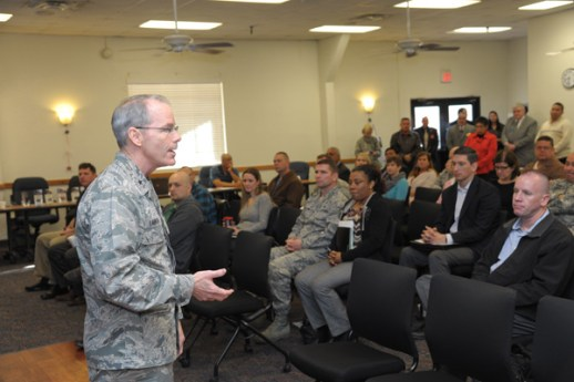 Photo of a military officer speaking to a room full of civilians wearing business suits