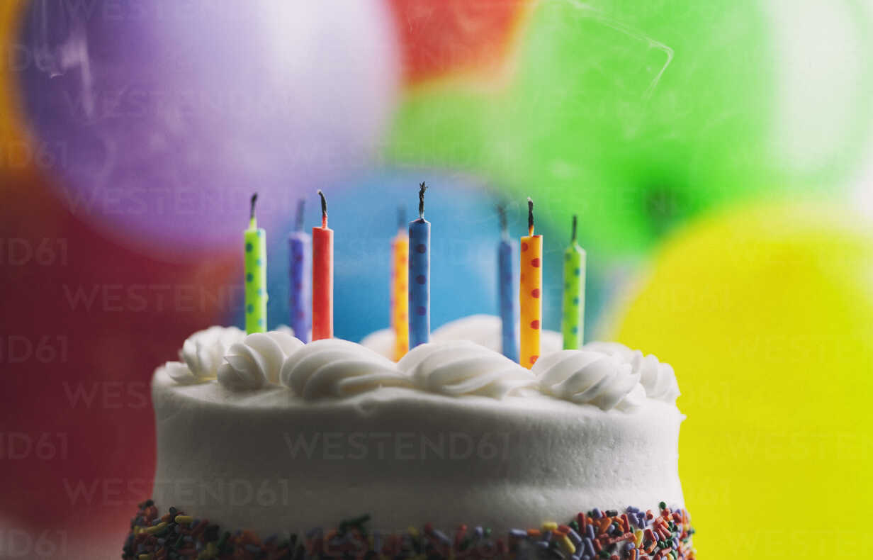 Blown Out Birthday Candles On A Cake In Front Of Balloons Stockphoto