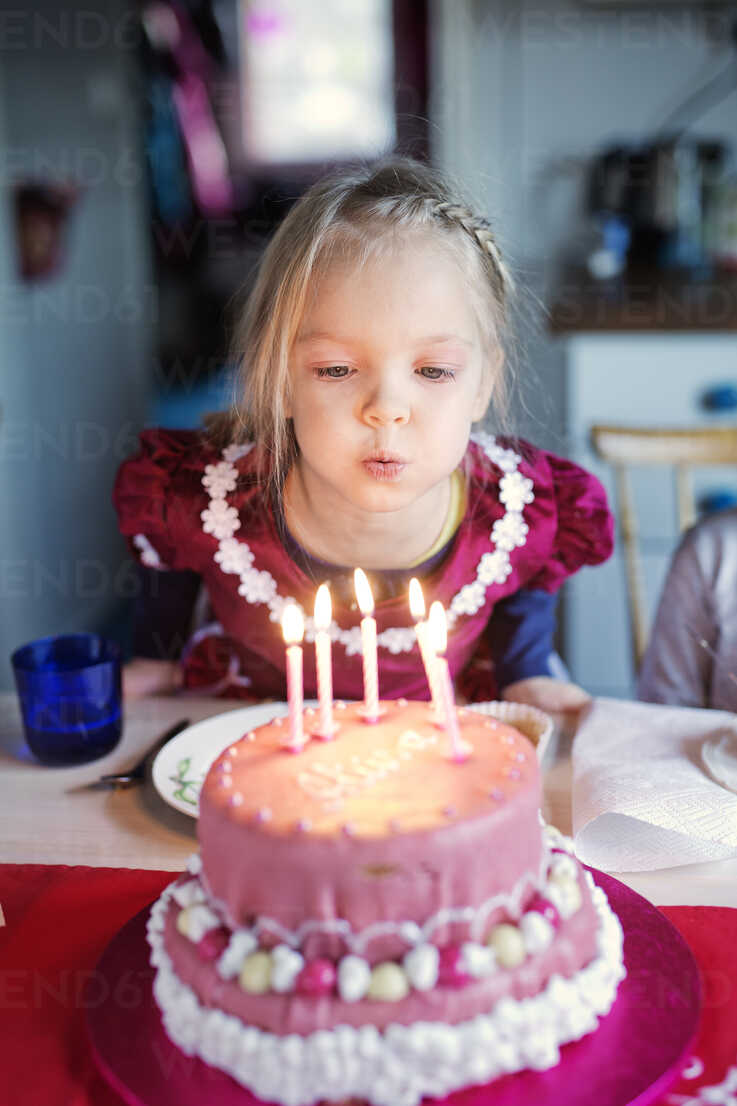 Girl Blowing Out Candles On Birthday Cake Stockphoto