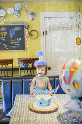 Baby Boy Wearing Party Hat With First Birthday Cake At Table Stockphoto
