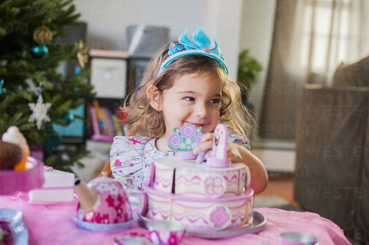 Female Toddler And Birthday Cake At Party Stockphoto