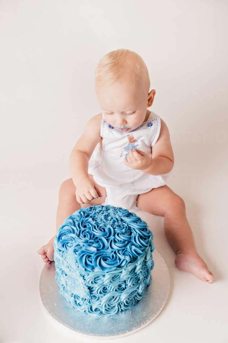 Baby Boy Testing Blue Birthday Cake Stockphoto