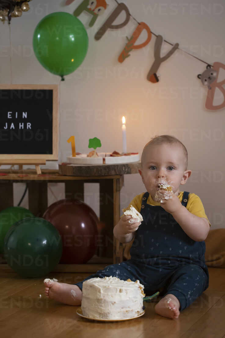 Hungry Baby Boy Eating Cake Of His First Birthday While Sitting Against Birthday Decoration At Home