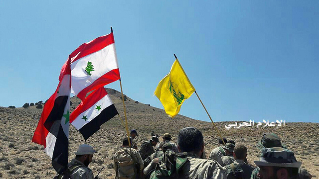 Hezbollah, Lebanon and Syrian flags on Syrian border (Photo: AP)