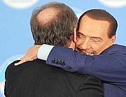 L'abbraccio tra Silvio Berlusconi e Roberto Maroni sul palco di Fieramilanocity (Ansa/Dal Zennaro)