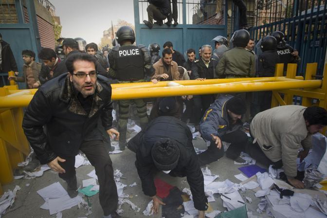 Centinaia di persone hanno fatto irruzione all'ambasciata britannica a Teheran. Molotov e sassi contro la sede diplomatica. La protesta contro le nuove sanzioni per il programma del nucleare iraniano. Nella foto manifestanti oltrepassano l'entrata dell'ambasciata (Reuters)