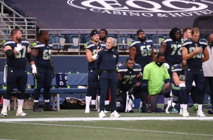 SEATTLE, WASHINGTON - SEPTEMBER 20: Seattle Seahawks coaches and players stand or kneel during the national anthem before the game against the New England Patriots at CenturyLink Field on September 20, 2020 in Seattle, Washington. (Photo by Abbie Parr/Getty Images)