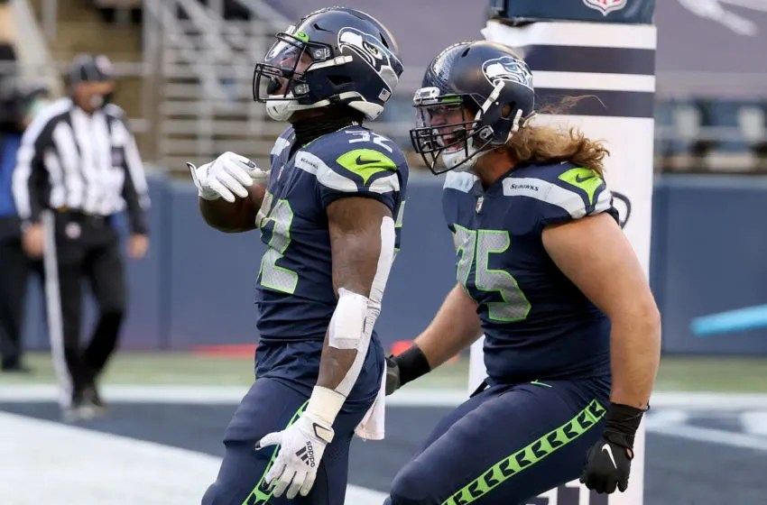 SEATTLE, WASHINGTON - DECEMBER 13: Chris Carson #32 of the Seattle Seahawks celebrates with Chad Wheeler #75 after scoring a 5 yard touchdown against the New York Jets during the second quarter in the game at Lumen Field on December 13, 2020 in Seattle, Washington. (Photo by Abbie Parr/Getty Images)
