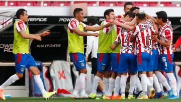 Chivas players celebrate a goal.