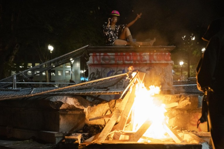 A protester sits where an elk statue used to stand during protests against racism and police violence in Portland, Ore., on July 16, 2020.  Jonathan Levinson/OPB
