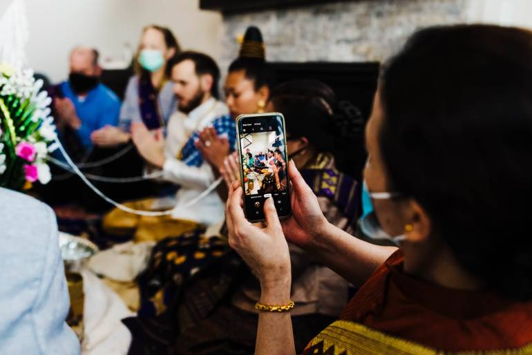 Family member captures cell phone photos during Traditional Lao wedding ceremony in St. Michael, Minnesota