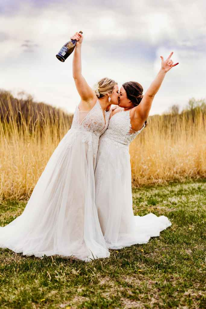 Minneapolis wedding photography showcases two brides kissing and with arms raised in celebration
