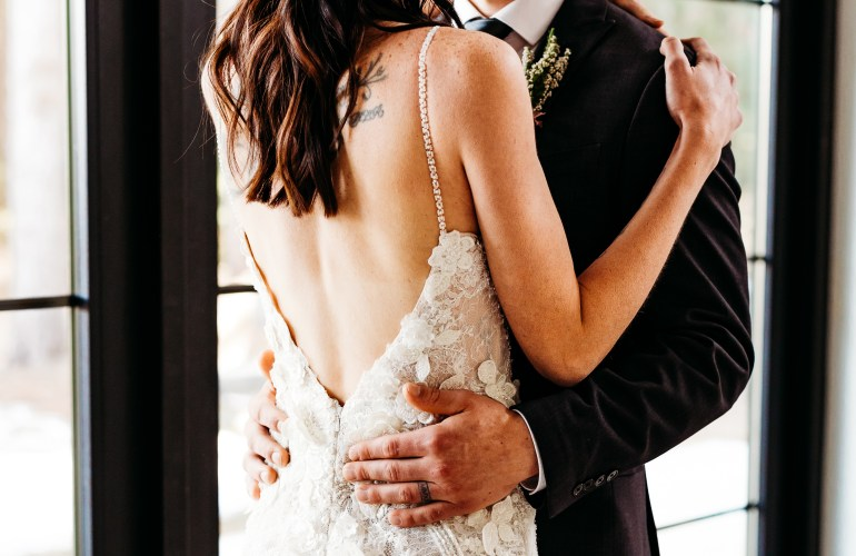 Bride and groom embrace inside Pinewood Weddings and Events in Cambridge Minnesota