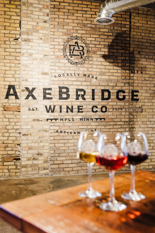 Glasses of wine sit out of focus in front of AxeBridge logo on wall during Minnesota Urban Winery Branding session