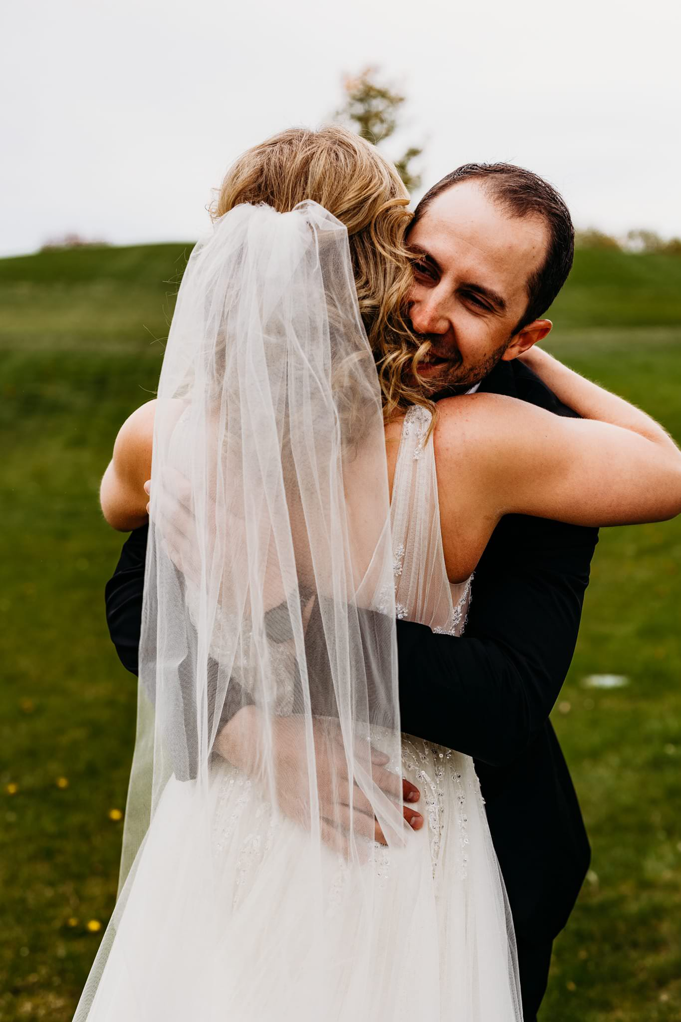groom hugs his bride after their first look at their hazeltine national golf club wedding