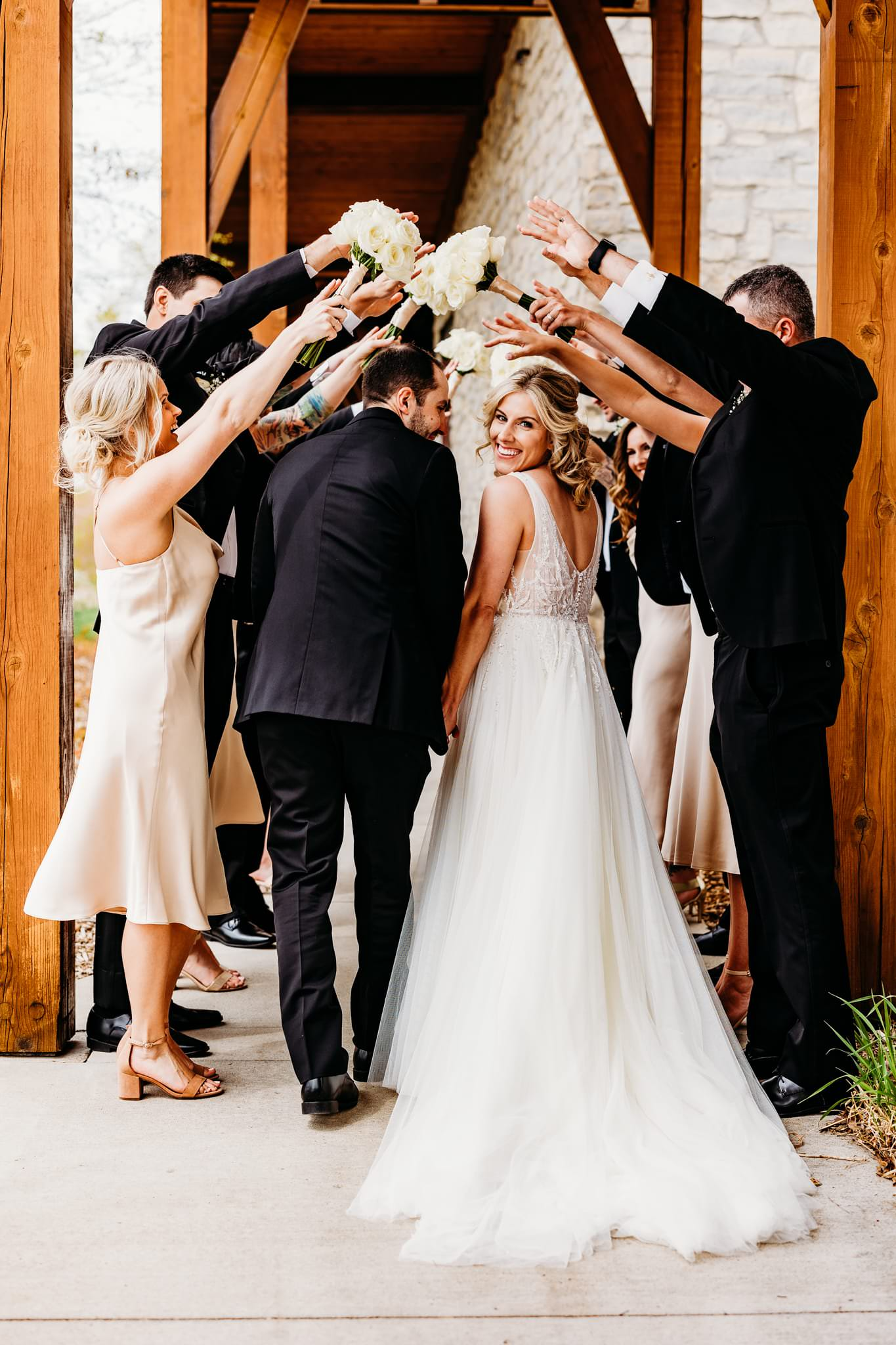 bride turns to smile at the camera while holding her groom's hand as they go to run through their friends whose arms are raised to make a tunnel at their hazeltine national golf club wedding