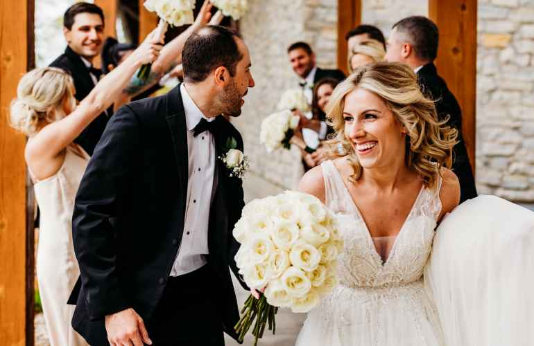 Couple runs through tunnel of wedding party's arms outside of the club house at their wedding at Hazeltine National Golf Club