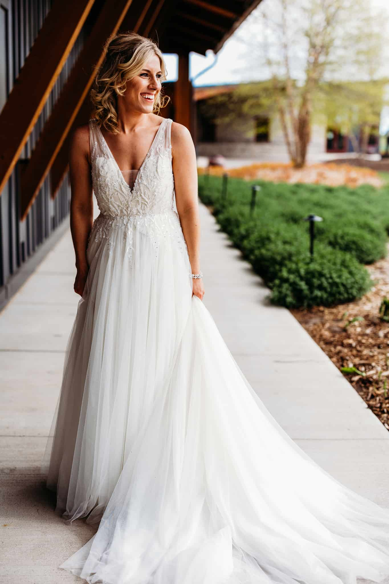 brides looks to her left as she poses outside the clubhouse at her Hazeltine national golf club wedding