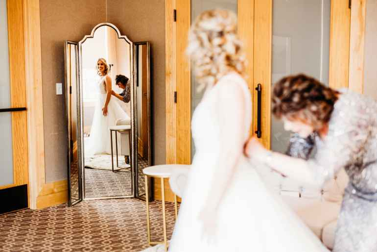 bride gets zipped into her dress by mom as she gets ready for her hazeltine national golf club wedding