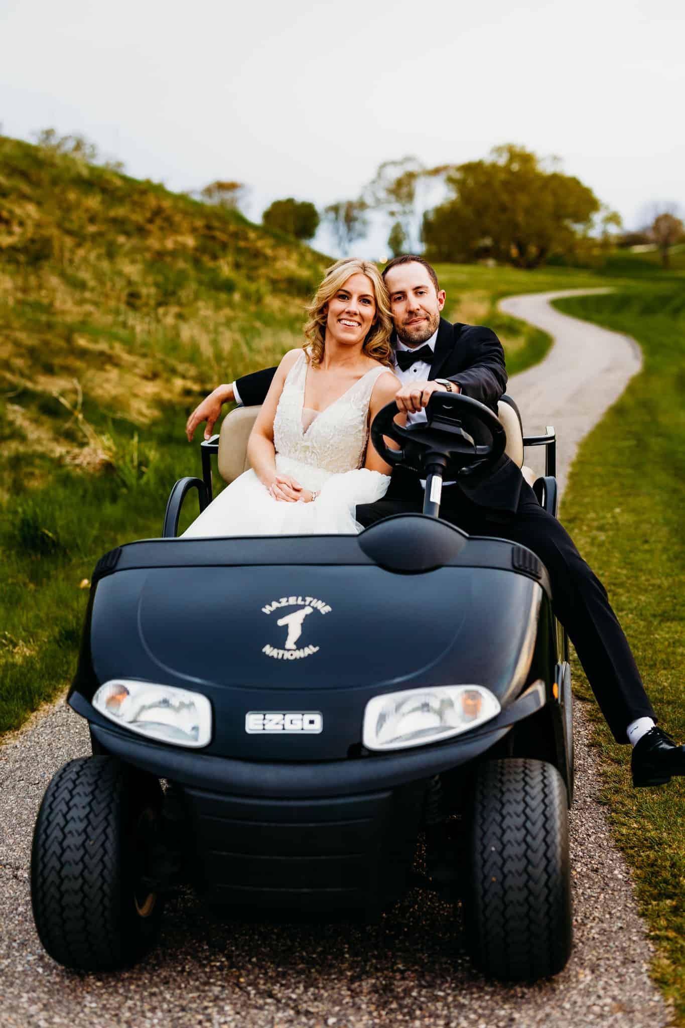 newlyweds pose in a golf cart at their Hazeltine National Golf Club Wedding