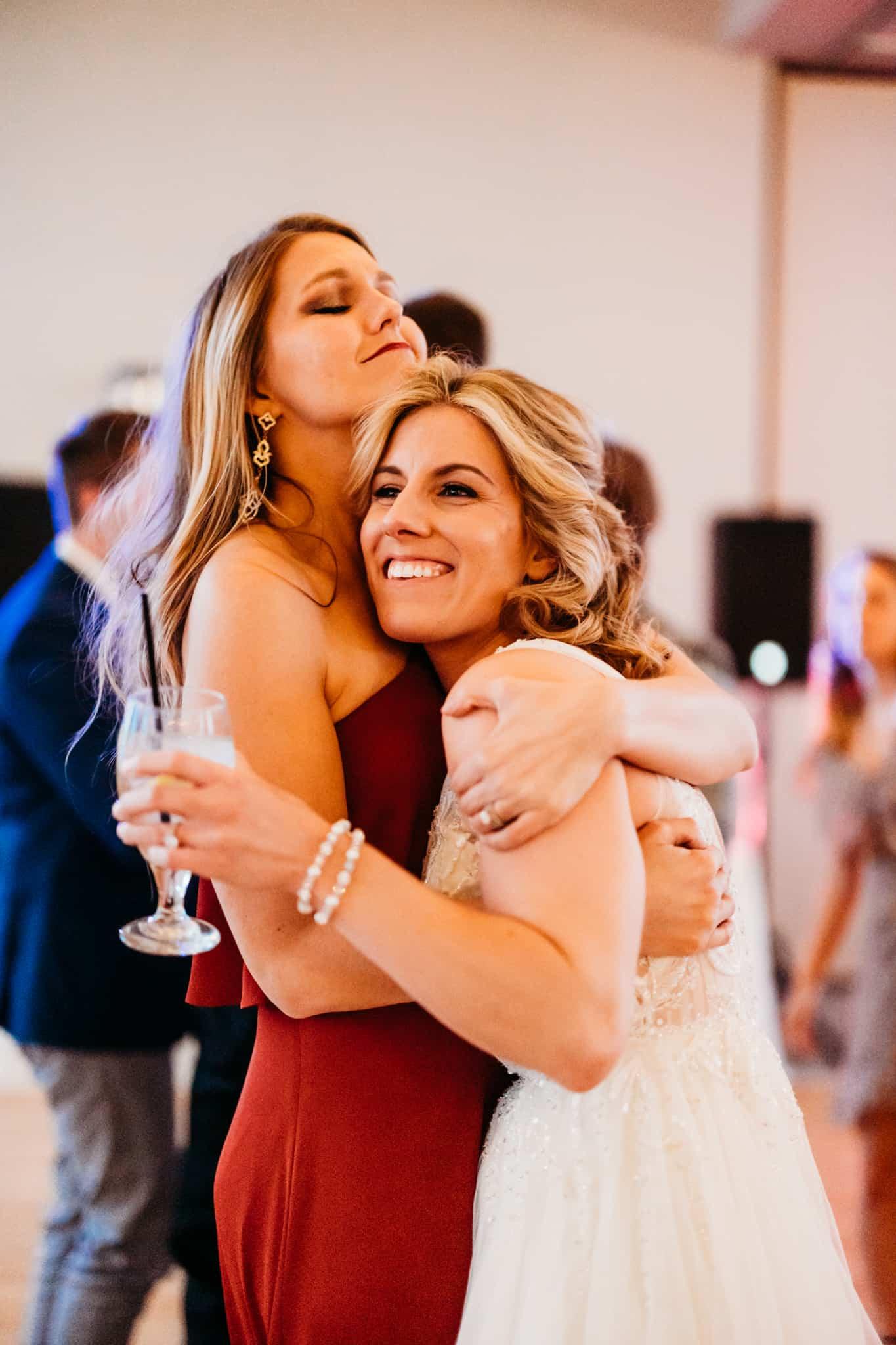 bride dances with a female guest at her hazeltine national golf club wedding