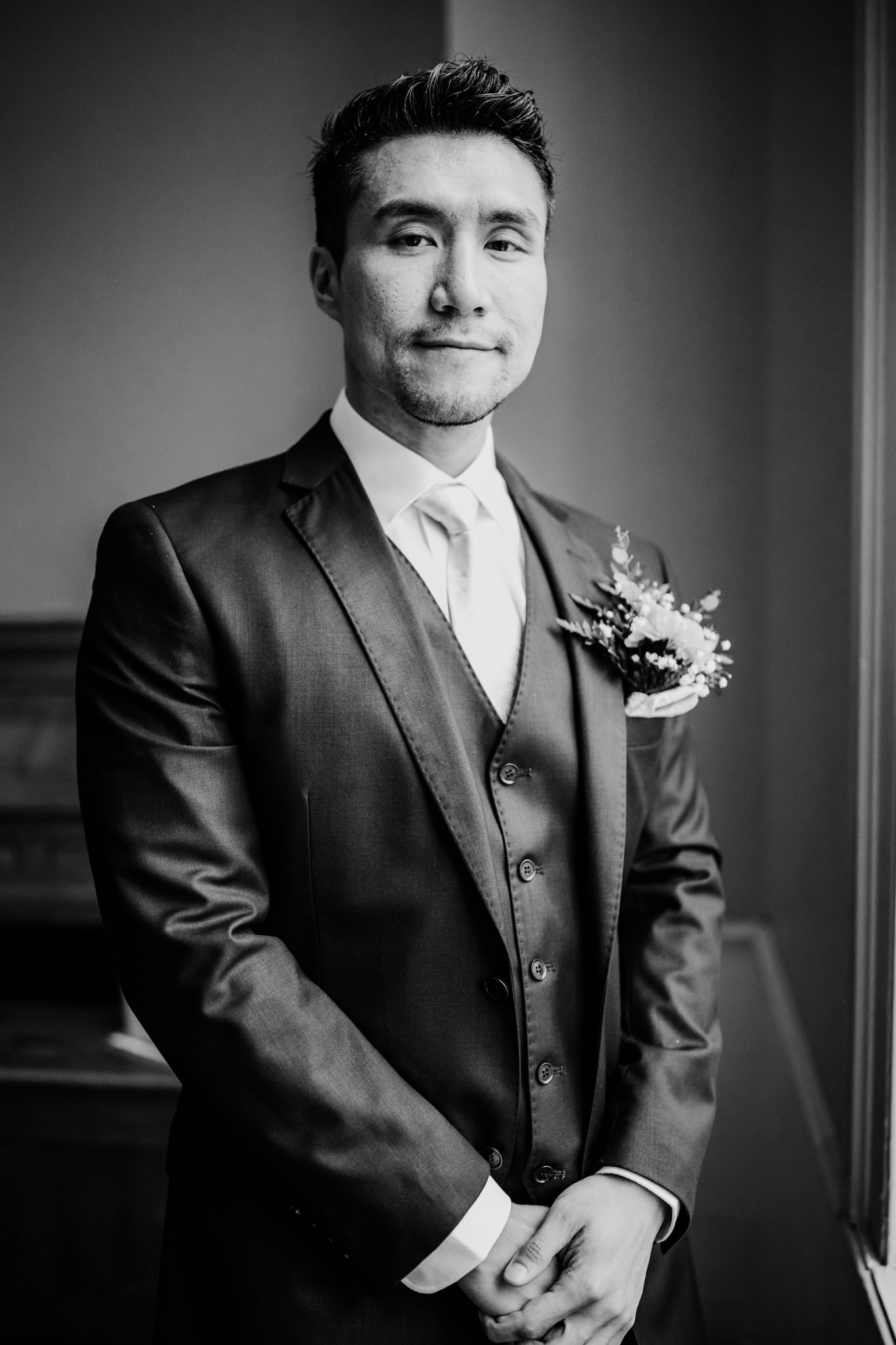 Groom poses near window in the chapel at his Mill Race Village Wedding