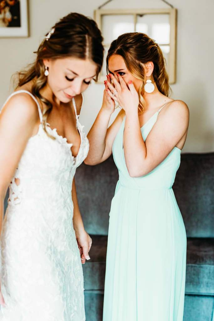 Little sister dries her tears after an emotional reaction to seeing her big sister in her wedding dress during their bridesmaid reveal