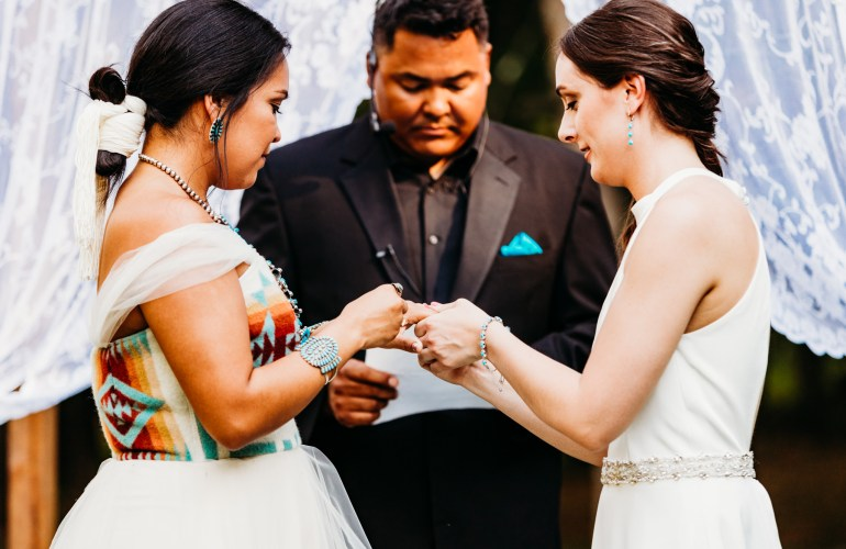 brides exchange rings at their native-inspired wedding