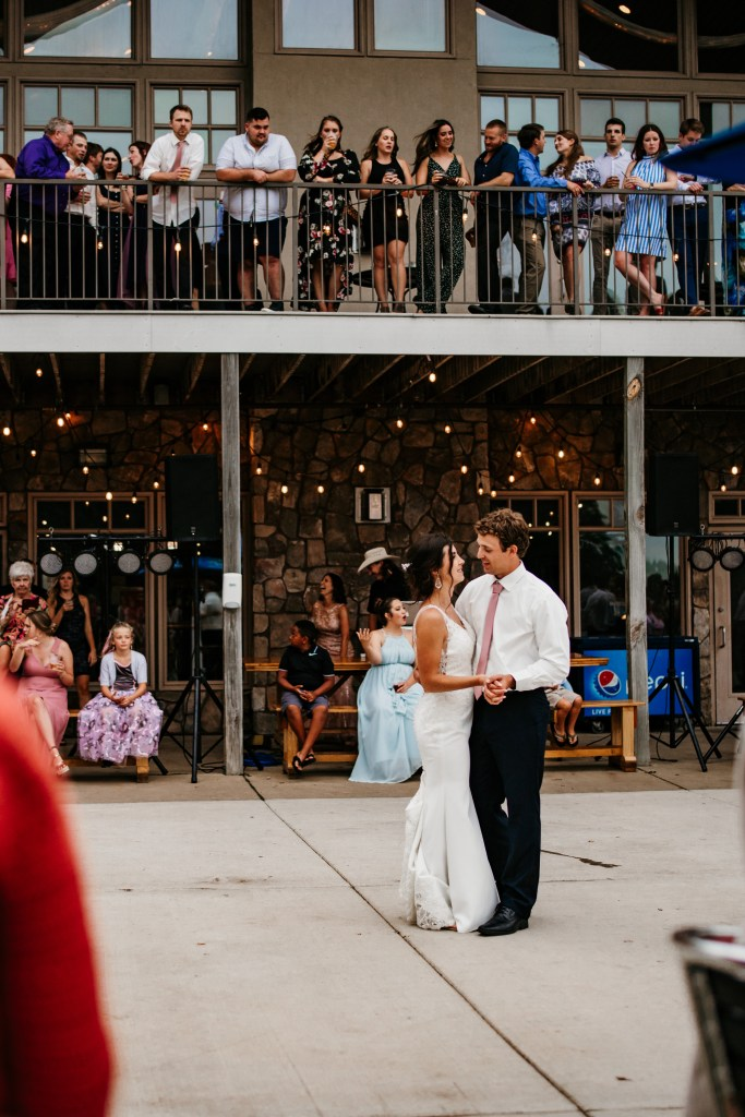 A couple dances together during their first dance outdoors