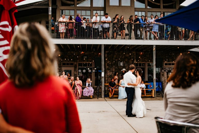 A couple dances together during their first dance outdoors as guests look on from patio and upper balcony