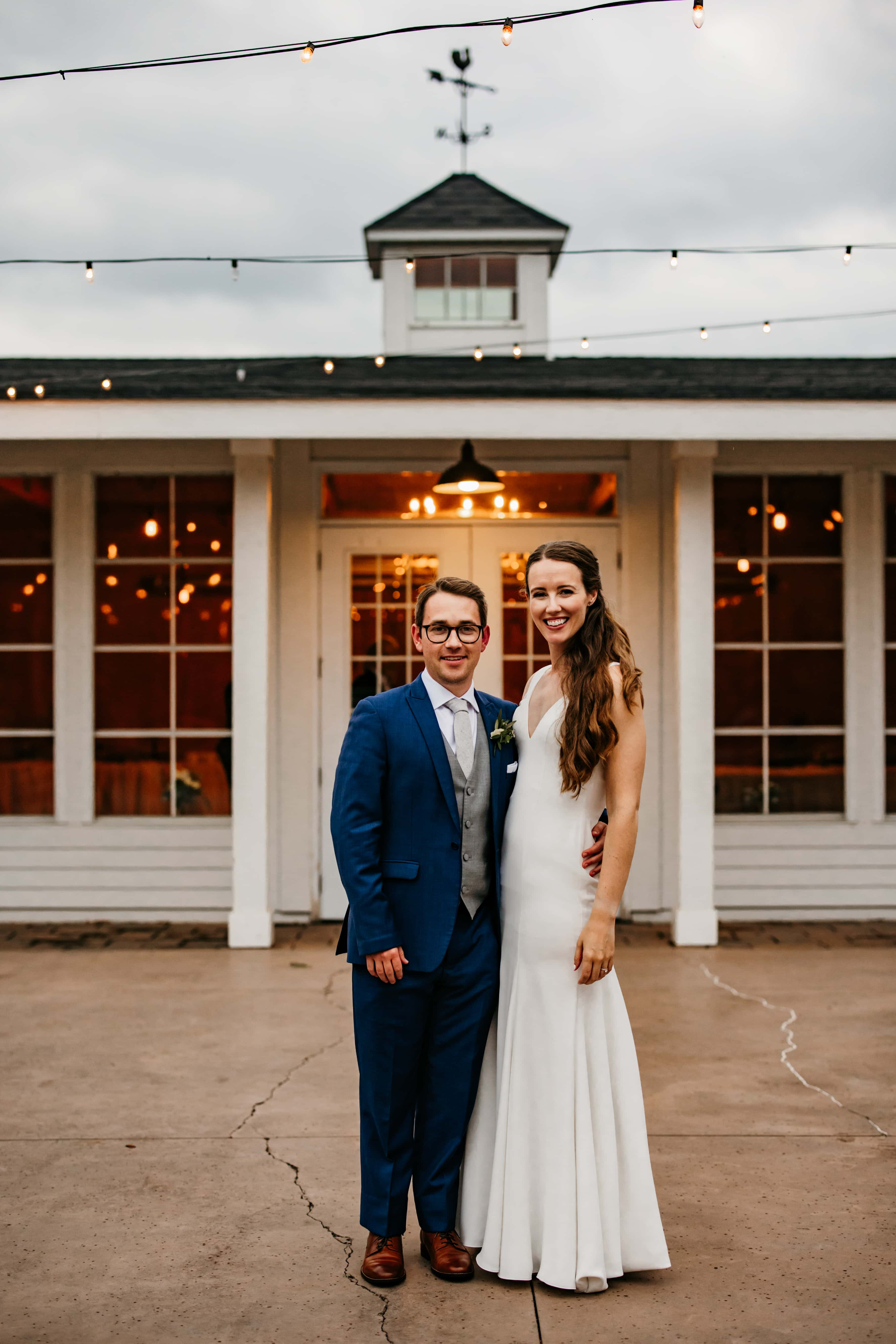 Couples stands together and smiles outside of their Rolling Ridge wedding at dusk