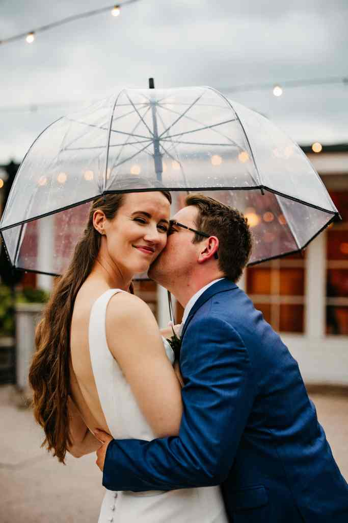 Groom kisses his bride under an umbrella outside of their Rolling Ridge wedding at dusk