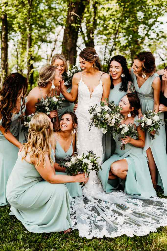 Bridesmaids crowd around bride and all smile at each other during Schroeder Farm wedding