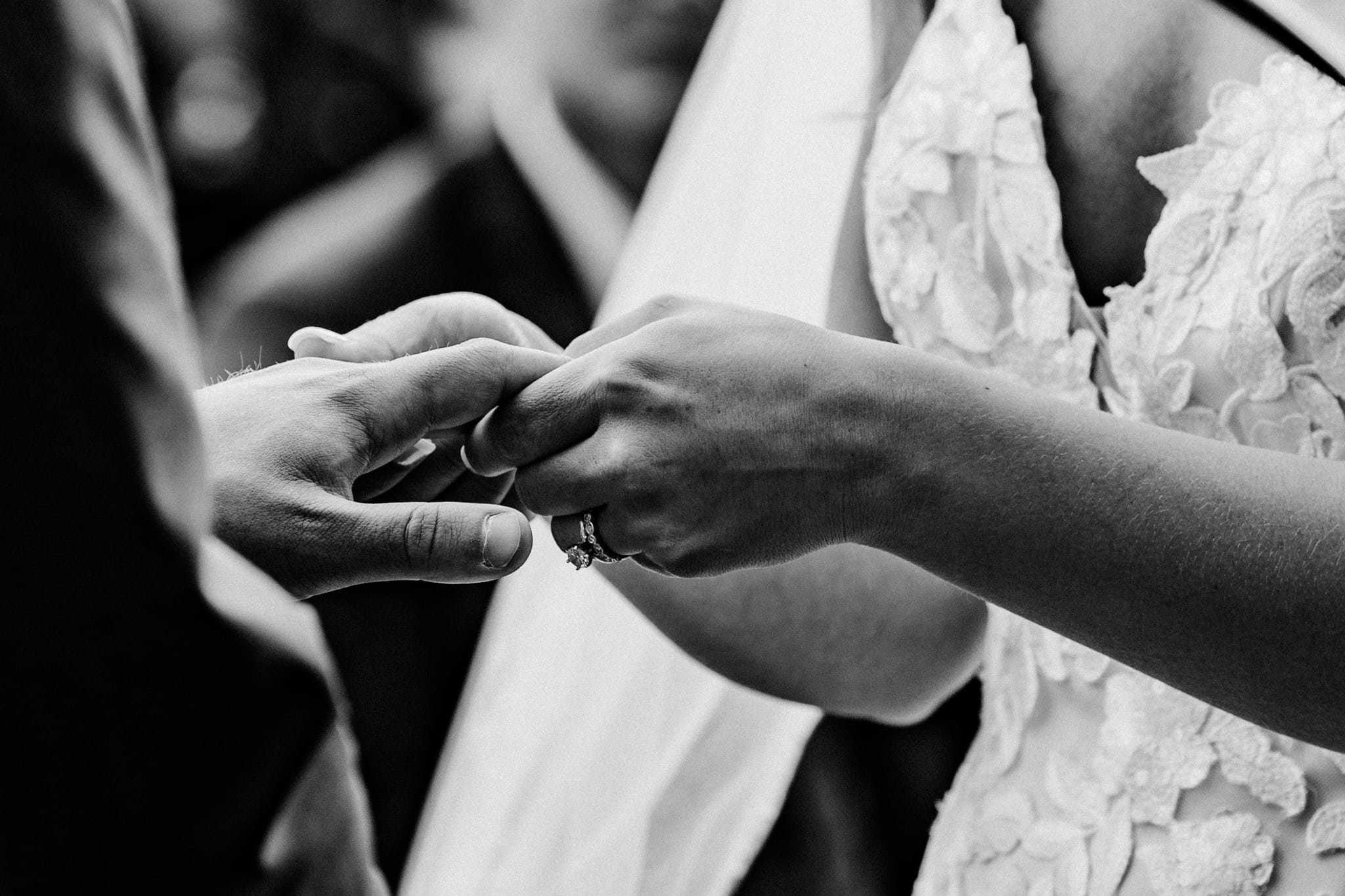 Couple holds hands as they exchange rings during their Schroeder Farms wedding
